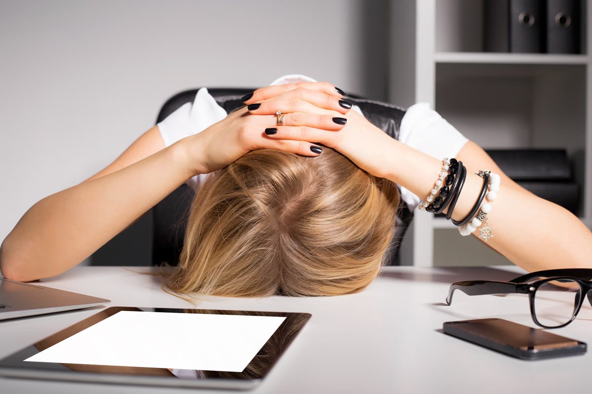 overwhelmed woman with head on desk